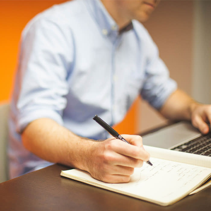 Photo of a man in the background his hand up close to the camera writing into a notebook.