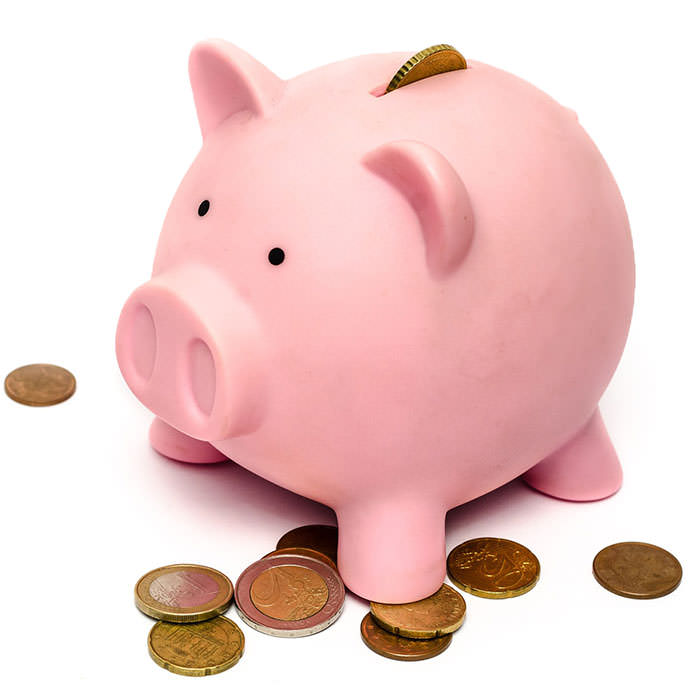 Photo of a big pink piggy bank with several coins around it and one coming out of it.