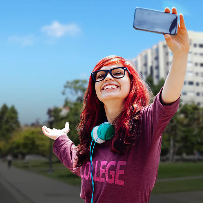 Photo of a young woman in front of her new College taking a selfie