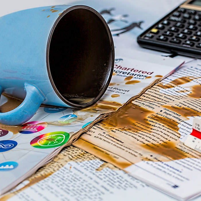 Photo of a cup of coffee spilled onto various papers