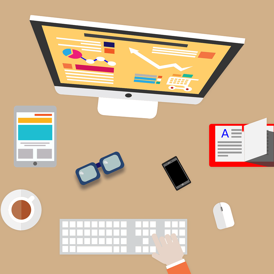 Clipart image of desktop computer with various graphs, a tablet, a book, cup of coffee, a phone, keyboard and mouse and a hand typing on the keyboard.