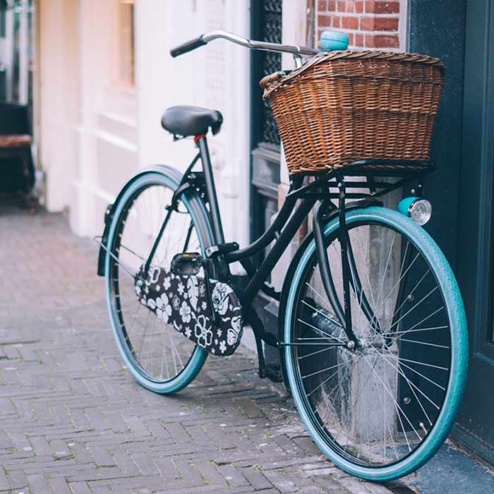 Photo of a black bike with blue wheels and basket out front of a building