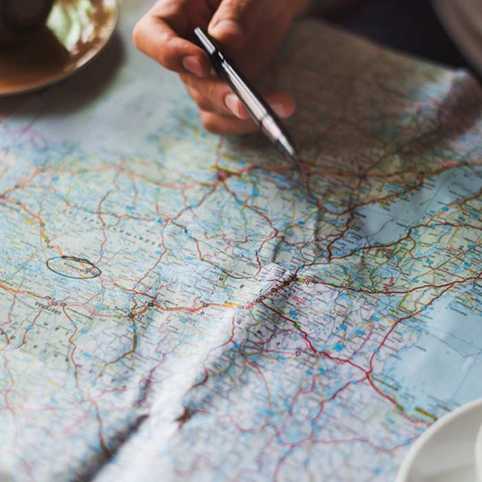Photo of a hand holding a pen over a map