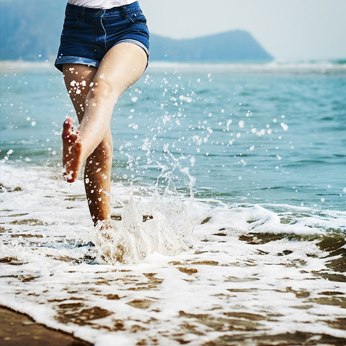 Photo of a persons lower half in the ocean kicking water in a joyful manner