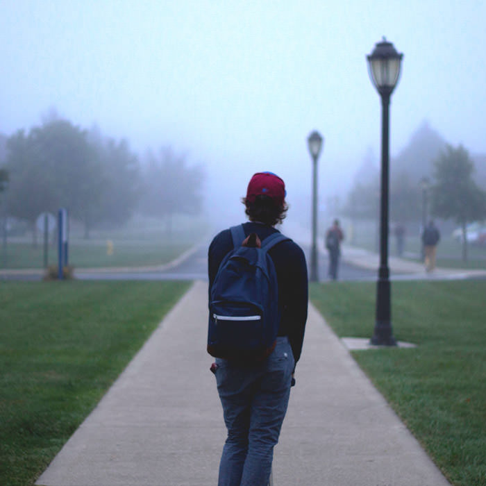 Photo of a young person in late teens facing away from the camera looking onto a college campus