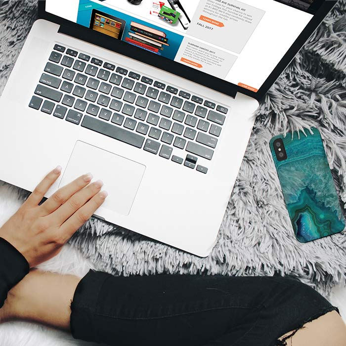 Photo of someone sitting on a bed using a laptop to browse College Ave Student Loans promotions web page