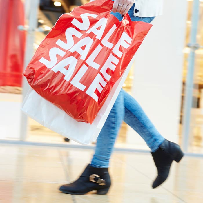 Photo of a woman holding a shopping bag that says sale three times on it